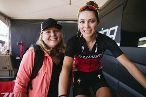 Kate Courtney on a trainer in the Specialized Racing tent poses with her mom